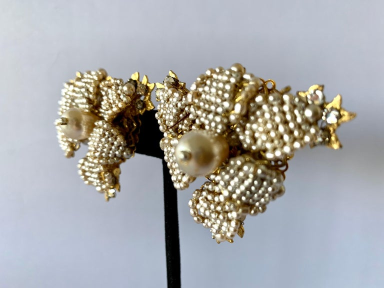 Vintage oversized clip-on earrings comprised out-of gilt metal, intricately beaded with small pearls and diamante rhinestones depicting detailed flowers. The earrings were created by William de Lillo and Robert F. Clark circa 1979/80, signed delillo.