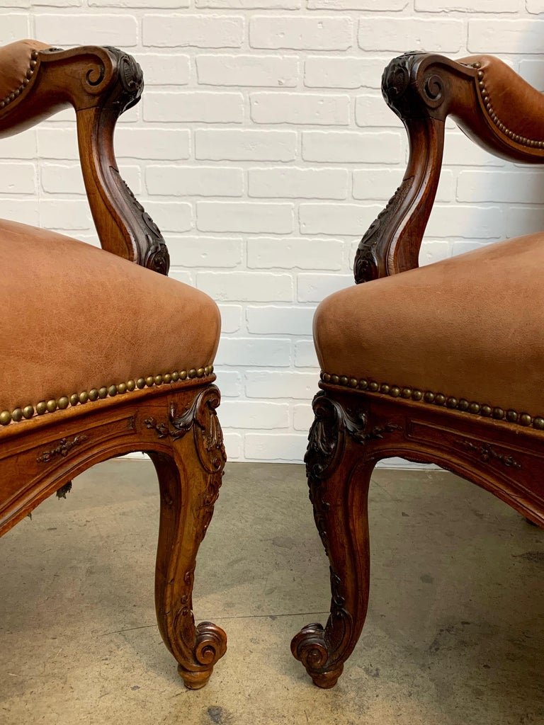 Pair of antique Louis XV style solid walnut throne lounge chairs with leather upholstery and brass nailheads.