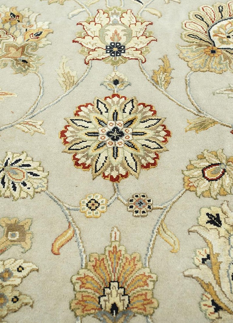 A beautiful oversized contemporary design carpet, hand knotted using finest wool and Chinese mulberry silk. On a light grey field, the design of Lotus blossoms standing next to each other executed in gold, silver and green tones. The light