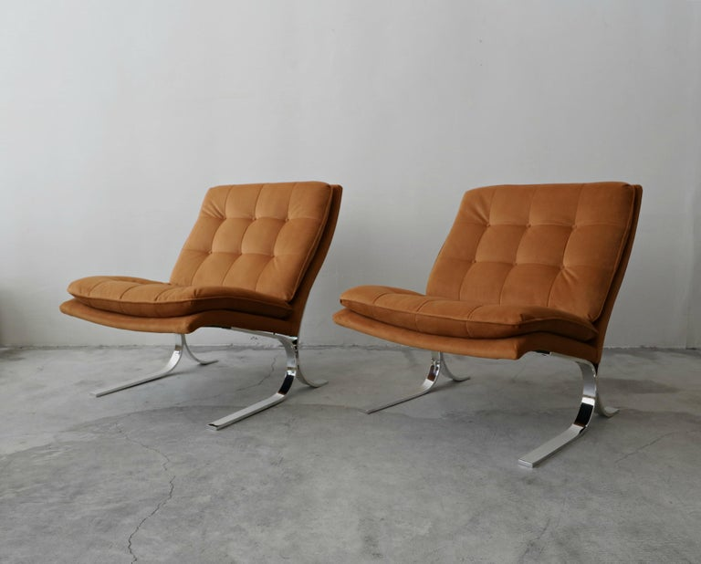 Beautiful pair of midcentury chrome slipper chairs. Chairs are reminiscent of the iconic Barcelona chair. These chairs are substantial in size and have the most beautiful profile.