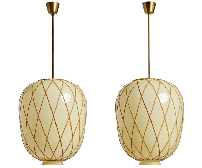 Oversized pendants attributed to Harald Notini for Bohlmarks, Sweden, circa 1930th. Handblown glass shade with vanilla exterior and opaline interior, with cane decoration and brass hardware. Single, Edison style socket. The shade dimension H 23.5