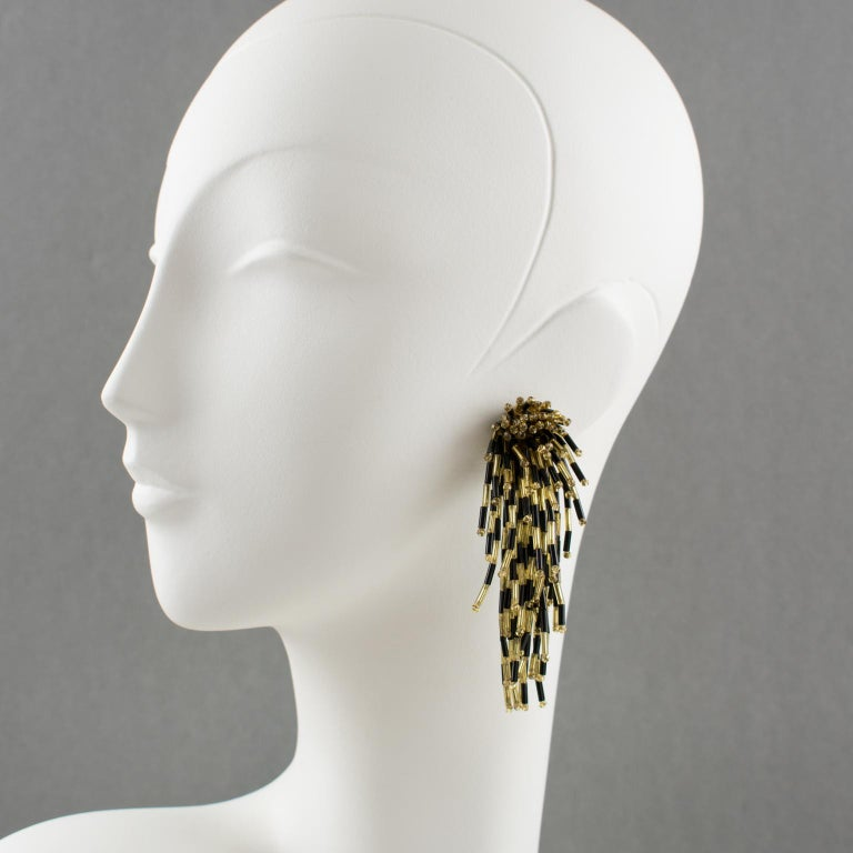 Stunning 1980s dangling glass clip on earrings with lion-fish shape. Oversized shoulder duster design with cascading waterfall shape build with tiny black and gold glass stick beads. No visible maker's mark. Measurements: 3.57 in. long (9.1 cm) x