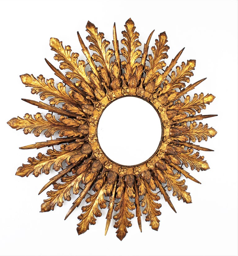 Massive 100 cm diameter baroque style hand-hammered iron leafed sunburst backlit mirror with floral decorations, France, 1930s. This outstanding and heavily adorned mirror has three tiers of leaves in different sizes and shapes combining Acanthus