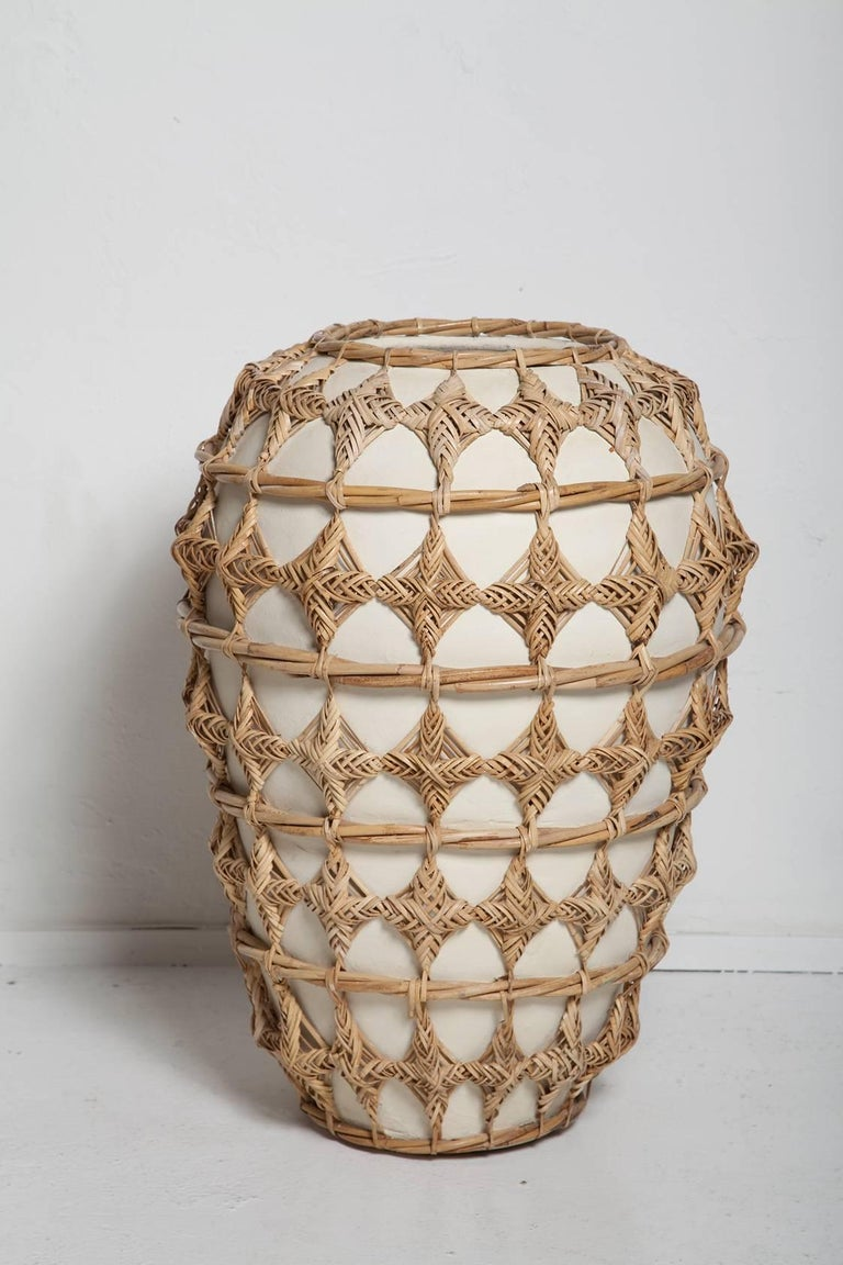A wonderful, white ceramic floor vase / urn intricately wrapped in woven rattan, a super summer statement piece!