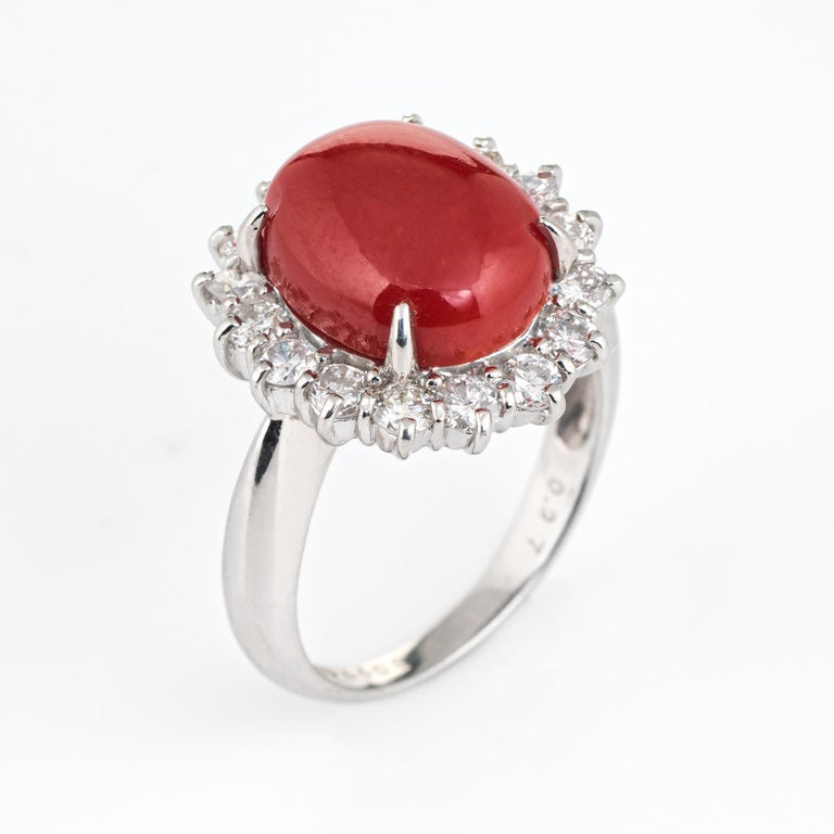 Elegant estate ox blood red coral & diamond ring crafted in 900 platinum.   Cabochon red coral measures 12mm x 10mm (estimated at 4.40 carats), accented with an estimated 0.97 carats of diamonds (estimated at G-H color and VS2-SI1 clarity). Note: