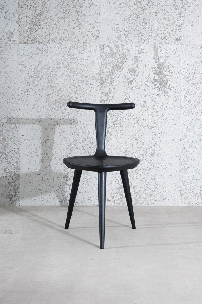 This listing includes one three-legged Oxbend chair in American ash hardwood stained charcoal black.  The original inspiration for the entire Oxbend collection, this modern dining chair was designed by Justin Nelson for Fernweh Woodworking. Born