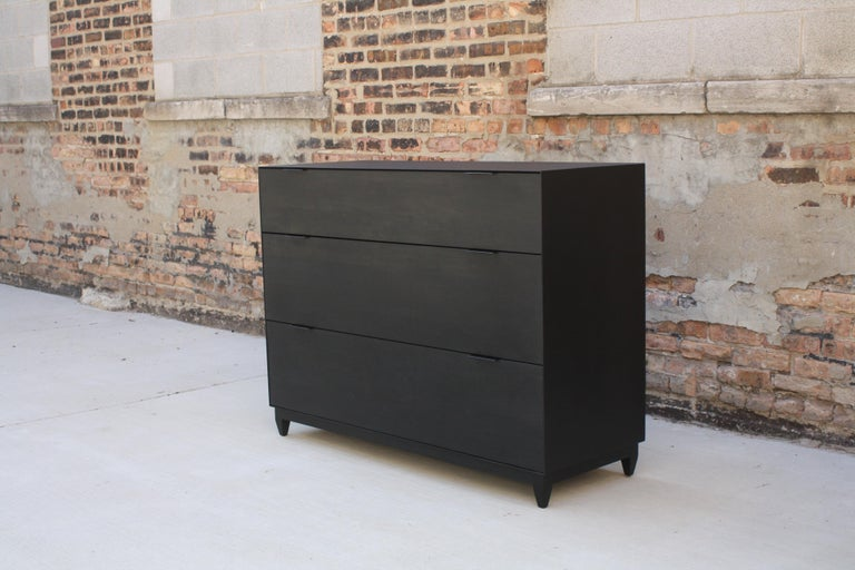 "Matte black steel and ebonized walnut  Shown with 3 sub-divided drawers - 48"" width x 32"" height x 18"" deep  A seamlessly welded case holds three sub-divided drawers on soft-close runners and sits on a solid wood base with punched saddle leather"
