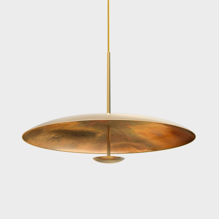 Two finely hand-spun brass plates make up this pendant light, finished in a mixed patina to create this unique antique appearance. Please note the process is random and each plate has a slightly variant finish. The light is projected into the shade
