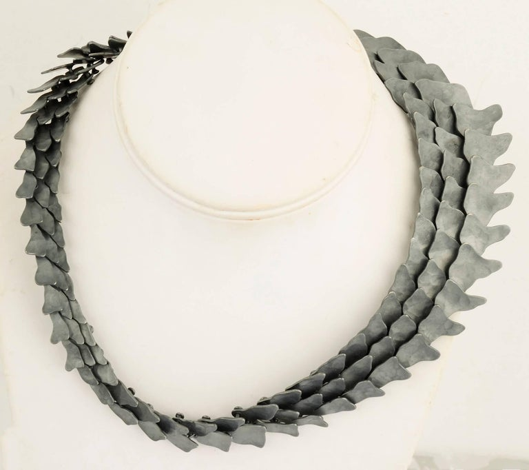 Architect Eduardo Herrera has translated his skills to jewelry making. This striking necklace is  made  of 950 silver, higher quality than sterling. The black has been oxidized to create the dark matte finish. Overlapping links are assembled with