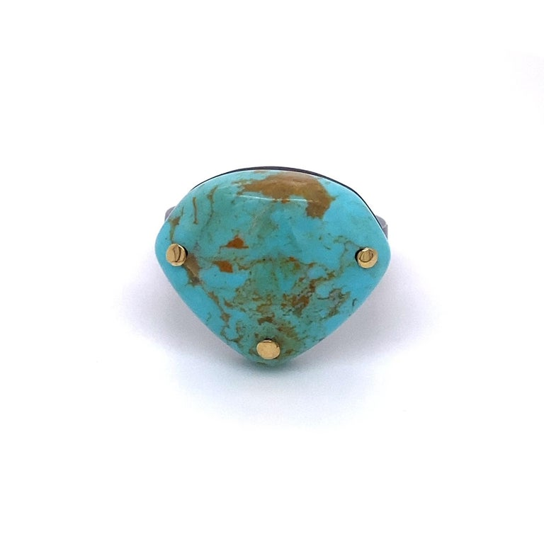 An oxidized sterling silver and 18k yellow gold with one shield shaped Kingman turquoise. Ring size 7.5. This ring was made and designed by llyn strong.