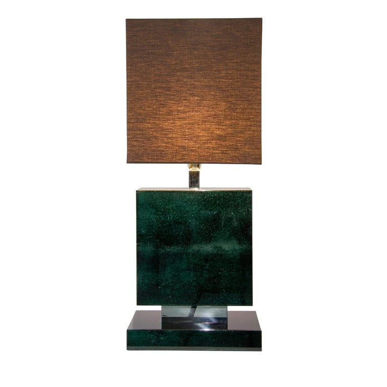 Captivating in design and bold in character, the oyster table lamp is covered with petrol colored parchment and features a superb high gloss finish. Combined with detail in polished nickel and a dark fabric lampshade, the elements all work together