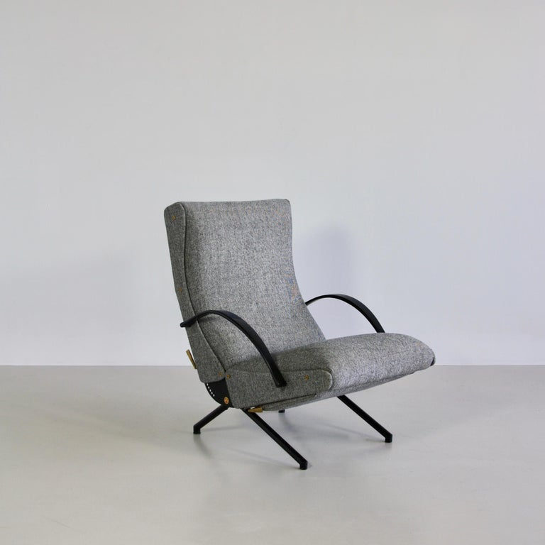 The 'P40' variable tilt armchair, produced by Tecno, Milan 1956. Black tubular frame with rubber armrests. Seat, back and footrest upholstered in yellow wool fabric. The footrest is stored under the seat. Brass detail.  The first edition of this