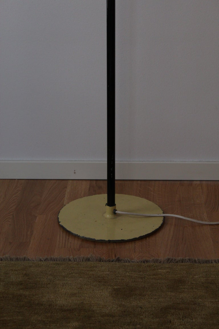 A table lamp designed and produced by Paavo Tynell for his own firm, Taito. Stamped with makers mark. Lacquered metal base, tubular metal rod, with black lacquer. Original raffia lampshade with brass details.   Other designers of the period