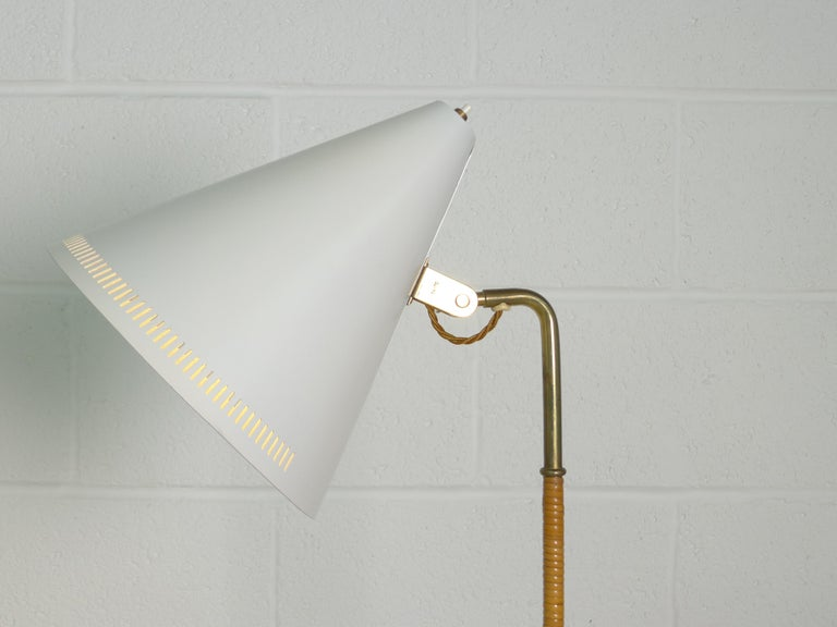 Paavo Tynell, Finland, 1940s, floor lamp of brass, cane and white enameled metal. Manufactured by the first and original maker, Taito Oy and stamped to the frame