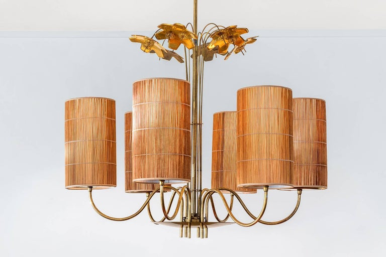 A large chandelier / ceiling lamp in brass by Finnish designer Paavo Tynell. Decorated with six snowflakes. Produced by Tynell's own firm, Taito OY. Handmade reed shades of later production. Six light sources.  Starting out as a jewelry designer,