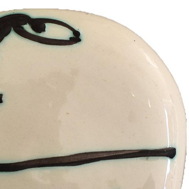PABLO PICASSO 1881-1973 Málaga 1881-1973 Mougins (Spanish)   Title: Divers  Plongeurs, 1956  Technique: Original Stamped Black Oxide Glazed White Earthenware Plate  Size (Diameter): 18.4 cm. / 7.2 in.   Additional Information: This original ceramic