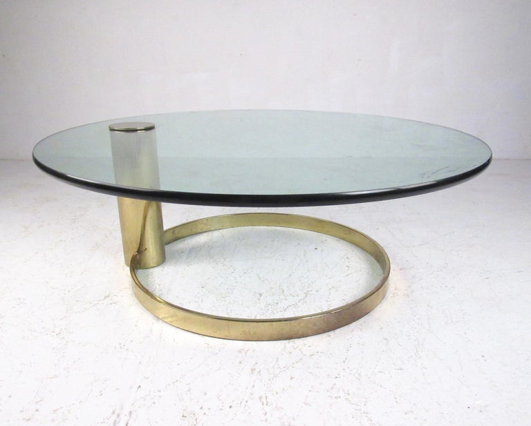 This striking vintage modern coffee table features brass plated cantilever base, thick glass top, and the striking midcentury style design of Leon Rosen for Pace collection. This circular brass plated coffee table makes an impressive addition to
