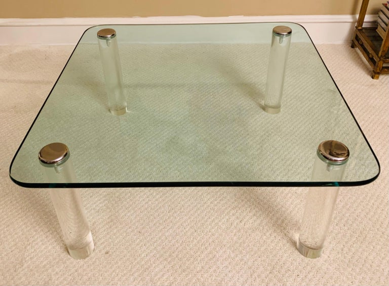 Large Pace Collection cocktail table with thick Lucite cylindrical legs.   Chrome is in extremely good condition, as is glass top.   Sleek and unobtrusive, it's hard not to love this piece.