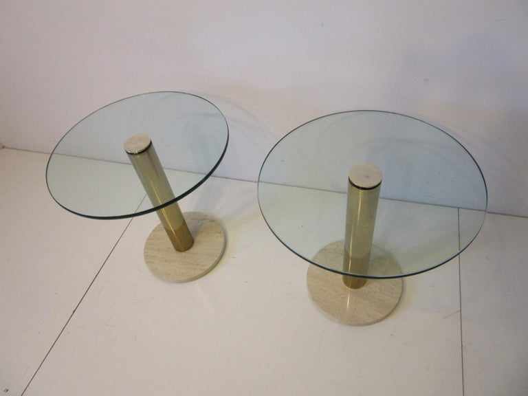 A pair of side tables with glass top having rounded edges, brass base and Italian Travertine marble bottom designed and manufactured by Leon Pace and the Pace Furniture Company. A staple of well designed interiors of the 1970s and 1980s for their