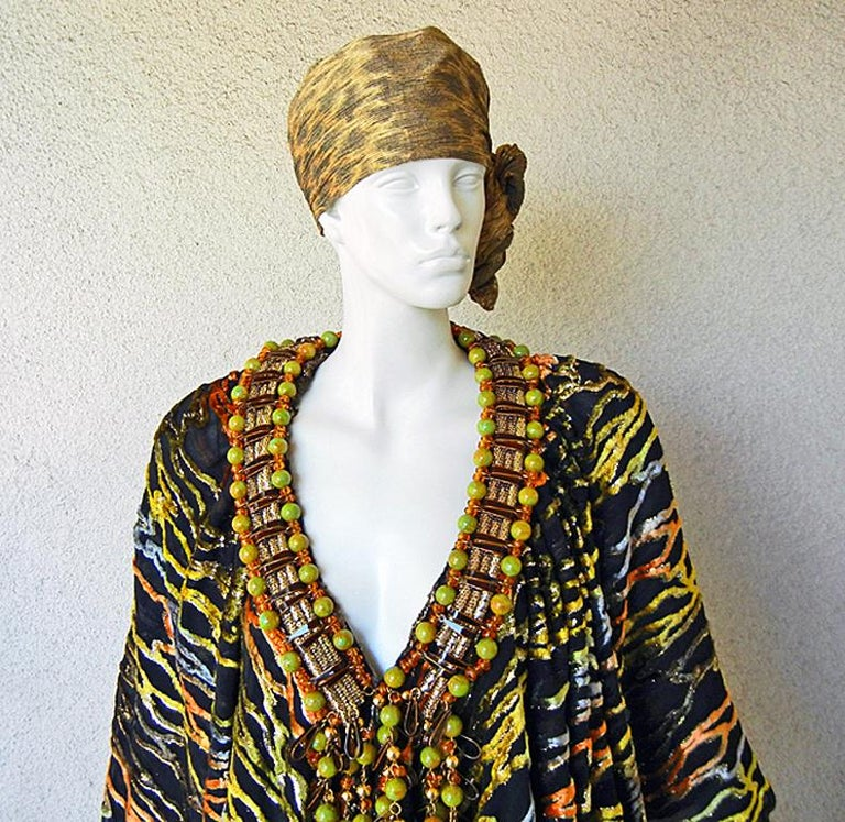 A one-of-a-kind Couture Paco Rabanne circa 1970's.  Fashioned of black burnout silk velvet with colors of orange, yellow, gold, in a zebra pattern. The attached oversized long Sautoir necklace adds to the drama and richness of the look.   The