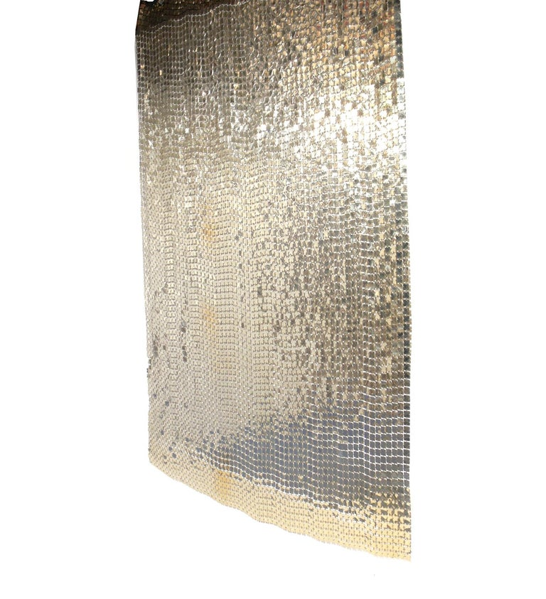 Paco Rabanne Space curtain or room divider, French, circa 1970s. It has a wonderful patinated aluminum color that looks more platinum or champagne color in certain light. Looks incredible when lit, as the discs reflect the light and gently move with