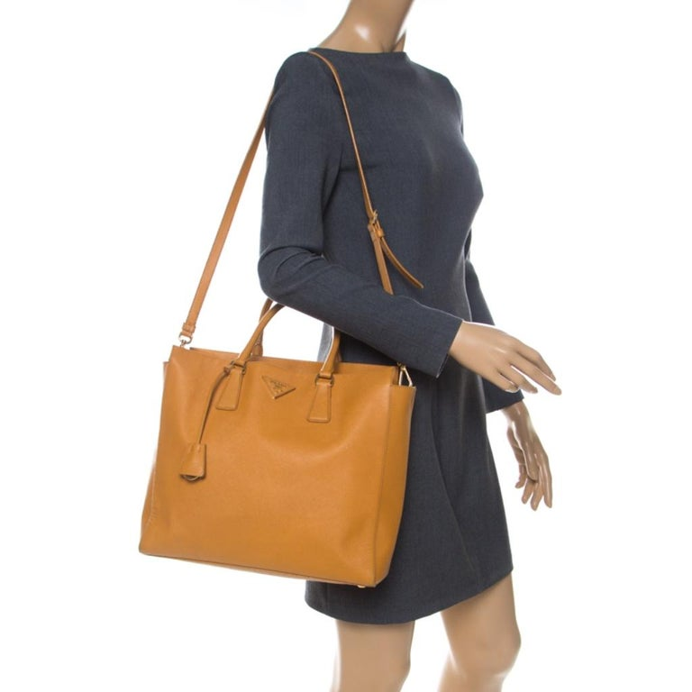 Masterfully crafted with orange Saffiano leather, this bag will make a memorable addition to your collection. Finely lined with monogram-printed fabric, this is a one-stop fashion adornment for all your needs! This Prada bag is splendid for everyday