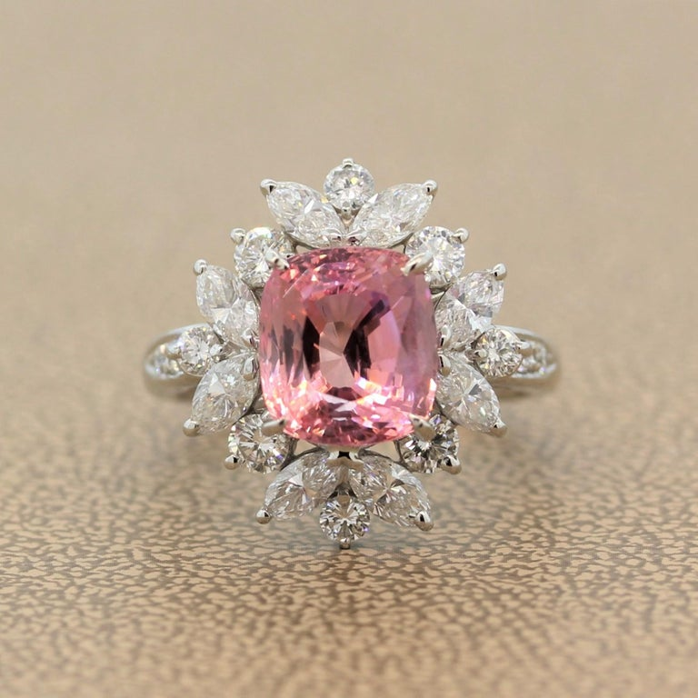 A stunning ring featuring a rare GIA certified 4.74 carat natural Padparascha sapphire. The pinkish orangy gem is from the original and most important source of Padparadscha sapphires, Sri Lanka. The gemstones is enclosed by a haloing cluster of