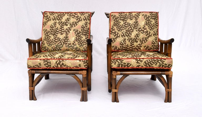A rare pair of Pagoda style lounge chairs by Calif-Asia Company Los Angeles California, of rattan, raffia, hardwood seats and original spring construction. The matching footstool retains the Calif-Asia tag. In marvelous vintage condition the set has