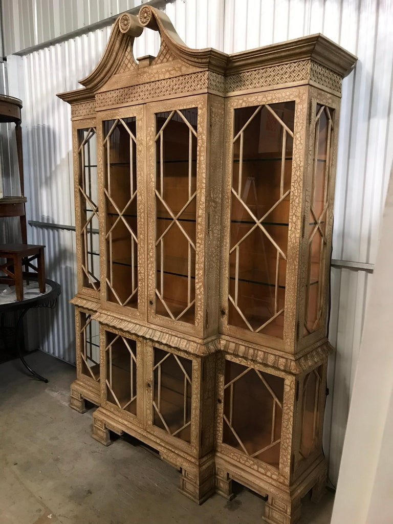 Very unique Pagoda style display cabinet with glass doors on both bottom and top. Both sections are illuminated. Beautiful fretwork detail trim.