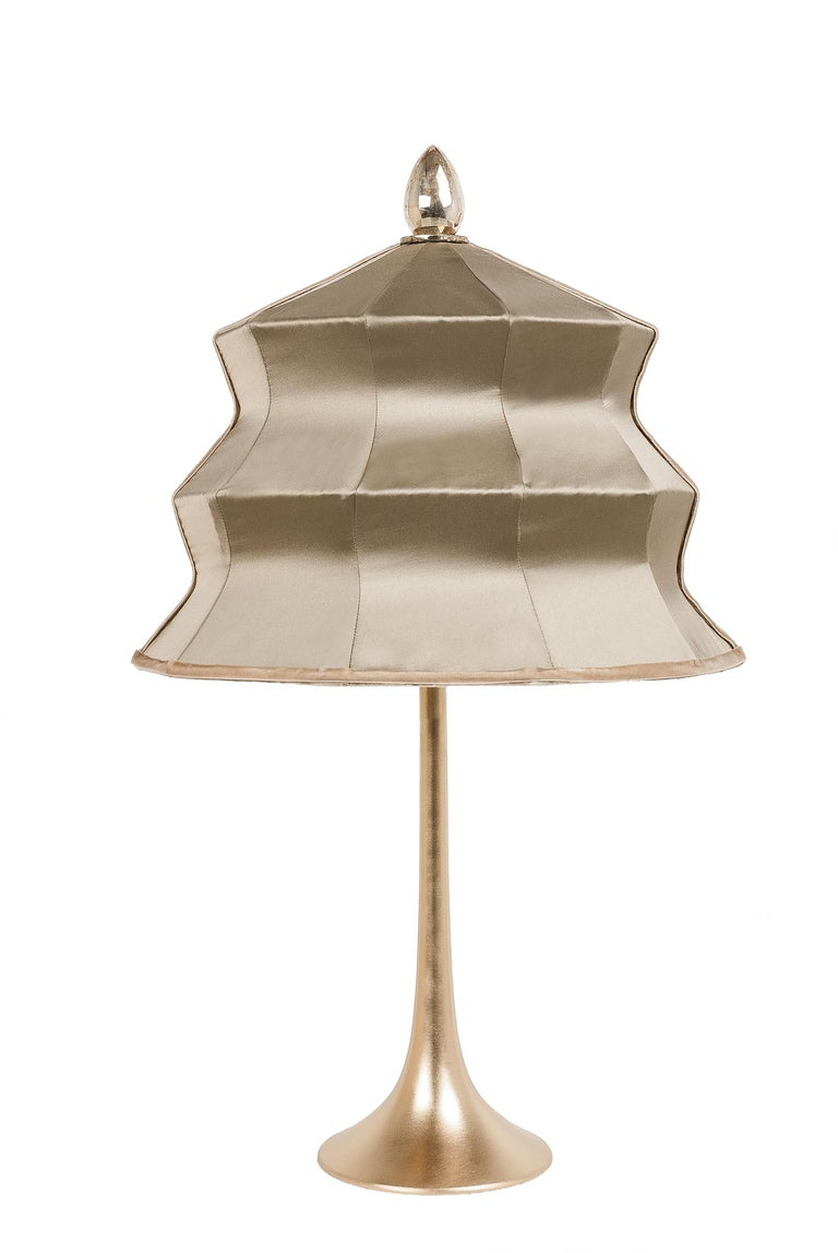 This table lamp is a contemporary piece, made entirely by hand in Tuscany Italy, 100% of Italian origin.   Inspired by the eastern Pagoda temple, Sabrina masterfully combines the geometric lines of the lampshade with the smooth, sinuous curve of