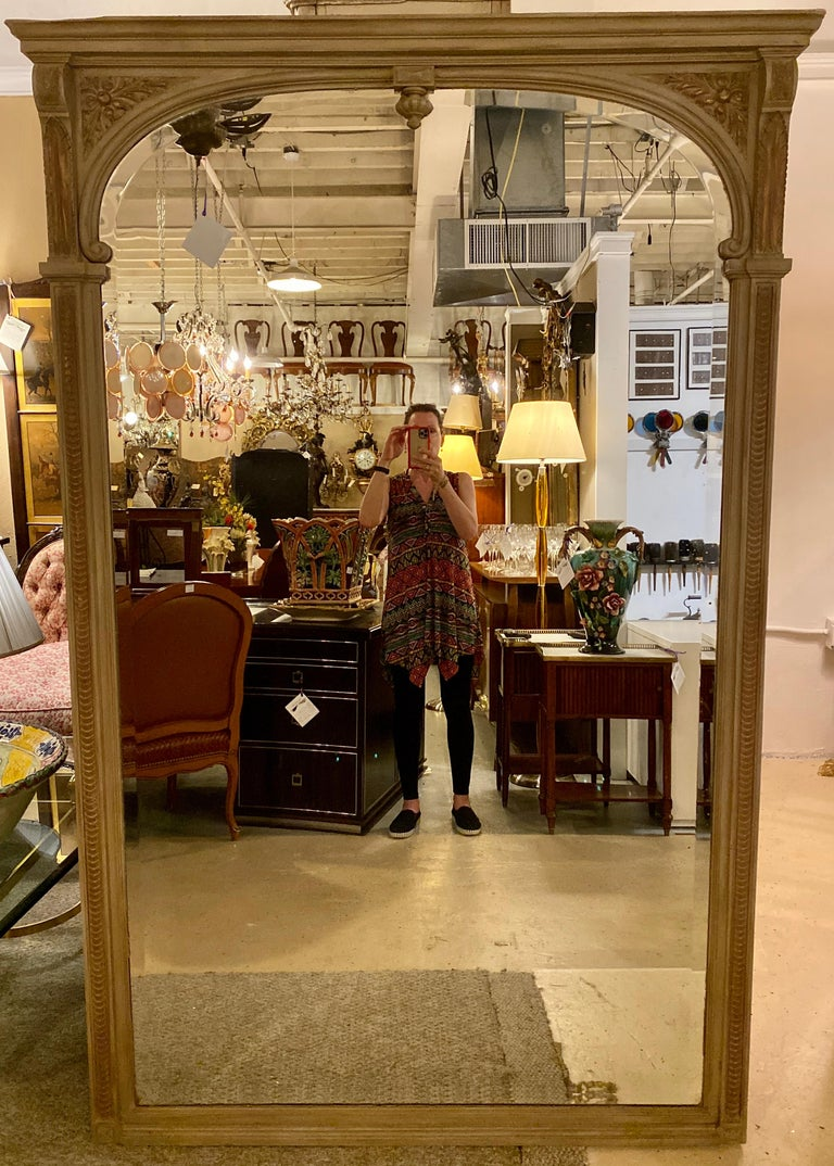 Paint decorated beveled floor or over the mantel (fireplace) mirror. Monumental. This is a very large and palatial carved hand painted Swedish style floor or over the mantel (fireplace) mirror. The beveled inset mirror on a finely carved and
