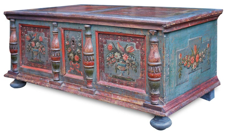 Painted alpine blanket chest  Measures (in cm) H. 49, L. 117, P. 58  Antique painted chest. Entirely painted in blue, on the front it has three mirrors with floral decorations and two colorful birds. On the sides we again find frames with