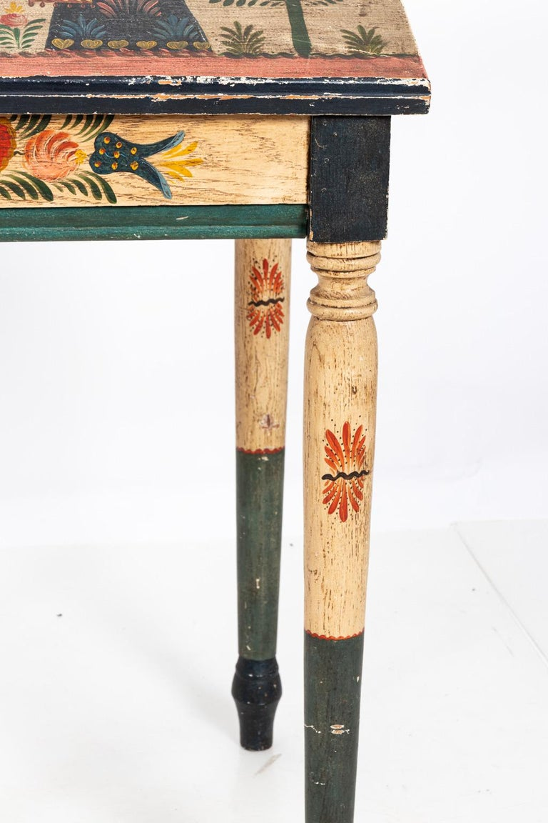 Painted Folk Art writing table detailed with flowers and figures throughout. Please note of wear consistent with age including paint loss and finish loss.