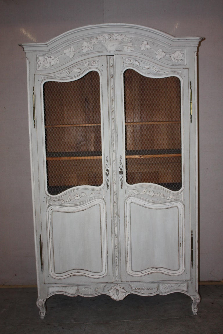 This is a very nice French painted armoire that dates to the late 1800s-early 1900s. It has a chicken wire upper panel on the doors. The shelves are adjustable.