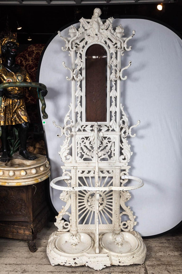 Cast iron, now painted white with some flaking. 6 double coat hooks, surround the mirror (mirror missing) Topped by a putto holding a torch and arrows. Sunburst pattern centered with flowers. Floral swags below mirror area. Umbrella resting area