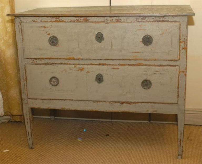 A two-drawer chest on tapered legs, this painted commode with original paint and hardware is from the period of Louis XVI.