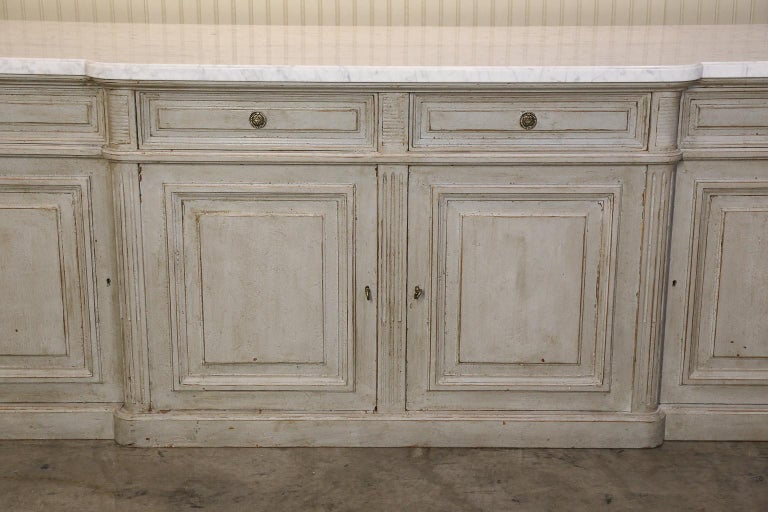 Very Large Louis XVI-style walnut credenza has been painted a grey wash and topped with a shaped white marble.  Credenza features four paneled drawers and cabinet doors for optimal storage.  Front ends of cabinet are simple columns with the marble