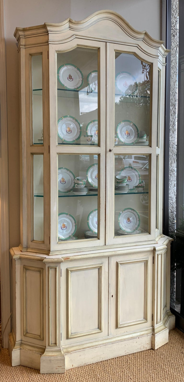 A tall and elegant mid-20th century. Paint decorated china or display cabinet with carved bonnet top and two glass doors revealing three substantial glass shelves above two cabinet doors offering additional storage.