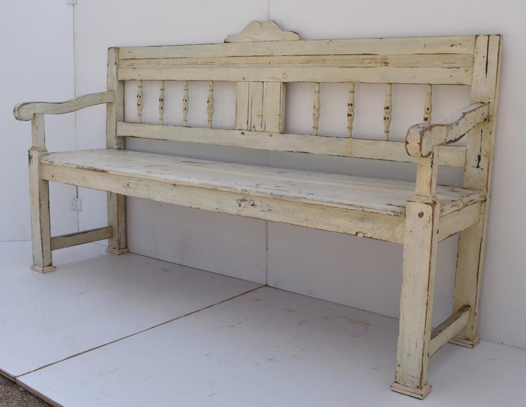 This rather stately pine bench has a small scallop cresting a bold top rail above a central faux paneled splat flanked by four turned spindles each side. The shapely protruding arms are supported by nicely tapered front legs. In old white paint worn