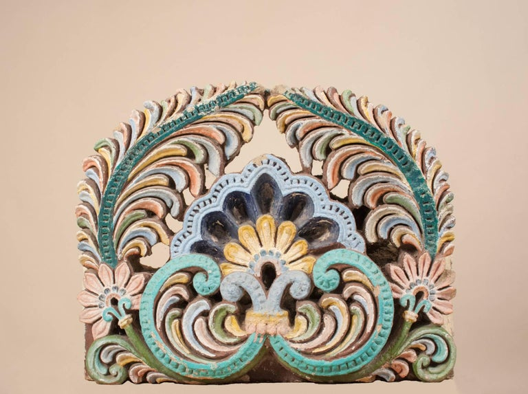 A large, authentic painted sandstone fragment from a Hindu temple in south India. More recently re-painted, this circa 1920 stone artifact is hand carved with a lotus flower and leaf design in a pastel palette mixed with darker greens and blues. The