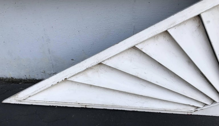 A splendid triangle form architectural transom or door fan with wooden louvers in a sunburst pattern with a molded edge surround, probably dating to the late 19th or early 20th century in white paint, with remnants of gray and red undercoats in very