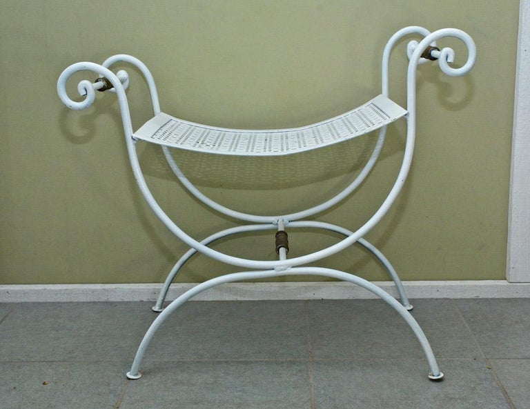 Midcentury wrought iron saddle seat bench can be used as vanity stool or for outdoor patio garden use. Scrolled arm support, metal mesh seat, attributed to Salterini, suitable for indoor and outdoor use, clean ready to use condition.  Measures: