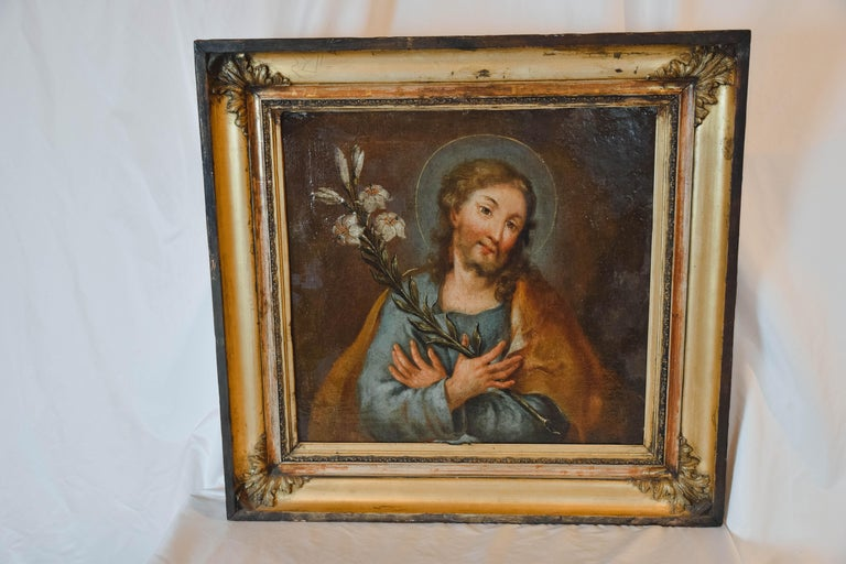 This beautiful oil on canvas painting of Jesus with his hands crossed over lilies was found in France. Although we could not find a signature, this piece was probably originally painted for the decoration of a church and has wonderful colors and a