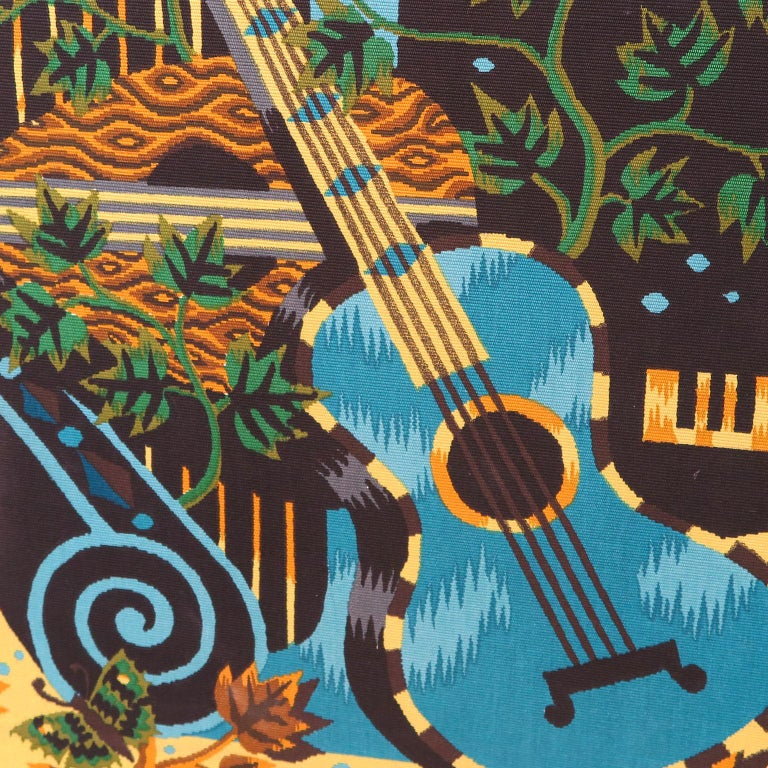 Large wall art of musical instruments with harp, banjo, guitar, and piano among a nature background with vines, birds and butterflies. Painted on wool textile. Signed Jean Picart Le Doux on the bottom. New black frame.