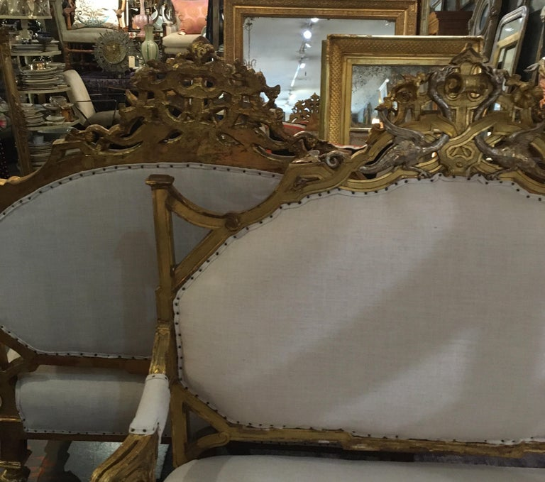 Pair of highly carved 1820-1830 gold and silver gilt settees. Hand carving features dragons and cherubs. These are beautiful and very useable. They sit very well and work well opposing each other or back to back.