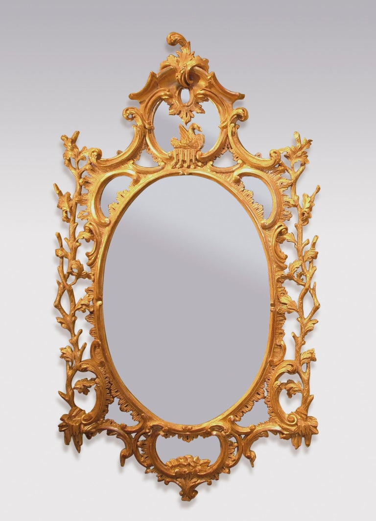 An important pair of mid-18th century period carved giltwood mirrors, having oval centres surmounted by scrolled and corniced panels with swans. The Mirrors decorated with C-scrolls, leaves and branches, with oval panels with rock decoration below.