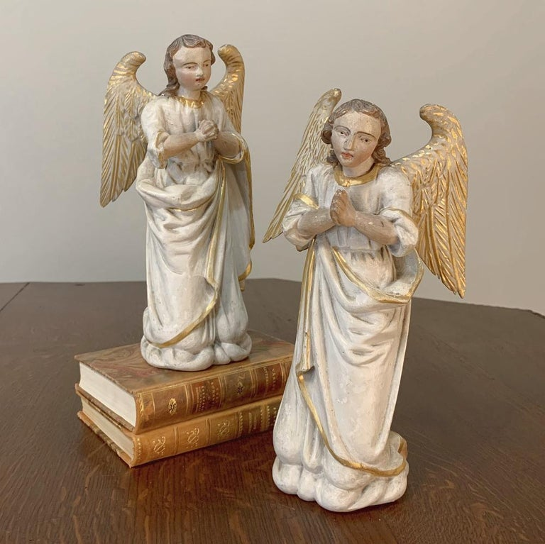 Pair of 18th century hand carved and painted Italian Angels were lovingly sculpted from solid blocks of wood, then carefully hand painted to depict a pair of gold-winged angels in pensive prayer. Such works of devotion were often created for private