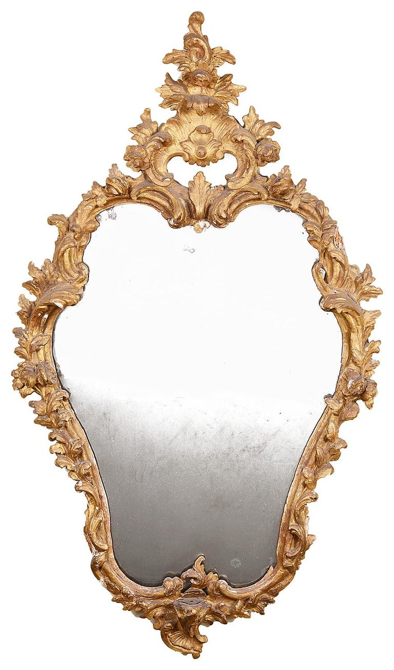 A very pleasing pair of 18th century Italian carved giltwood pier glass wall mirrors, each with carved scrolling foliate and floral decoration, both with their original mirror plates. Measures: 94cm (37