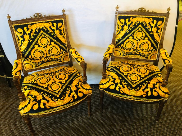 Pair of 19th-20th century Louis XVI style finely carved armchairs in Gianni Versace Fabric. These spectacular one of a kind antique walnut fauteuils or arm chairs would look breathtaking in any office or living room setting. The reeded Louis XVI