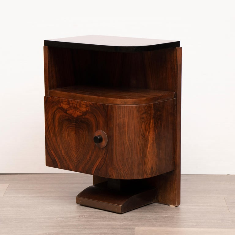 A pair of French 1930s Art Deco Walnut bedside tables or nightstands. The tops of each table have recently been refinished with a black lacquer paint. A space sits beneath each top where magazines can be stored. A single door opens on each cabinet